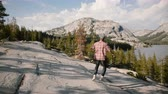 雄大な : Camera follows young happy tourist man running down big rocks while hiking alone at Yosemite mountain lake slow motion. 動画素材