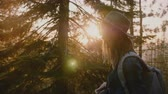 雄大な : Side view close-up shot of tired tourist girl with long hair walking on forest road on sunset Yosemite park slow motion.