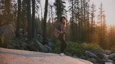 雄大な : Camera moves around excited tourist girl standing on big rock in deep woods of Yosemite on incredible sunset slow motion 動画素材