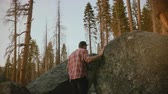 espíritos : Camera follows young local man hiking, climbing up on big forest stones to watch epic sunset at Yosemite slow motion.