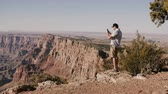 gran apertura : Happy young tourist man taking smartphone photo of epic summer scenery standing over incredible Grand Canyon USA.