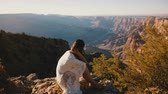 gran apertura : Camera zooms in on peaceful young woman with flying hair watching epic sunset panorama over Grand Canyon slow motion.