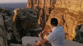 gran apertura : High angle camera moves over happy young adult tourist man sitting on big rock watching sunset scenery over Grand Canyon