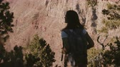 gran apertura : Amazing cinematic shot of happy young female tourist with backpack watching epic summer scenery of Grand Canyon ridge.