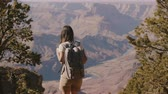 gran apertura : Happy beautiful young woman with backpack walking up to amazing summer landscape scenery of Grand Canyon slow motion.