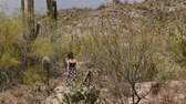 tucson : Slow motion back view young tourist woman walks among big Saguaro cactus desert field and hill in Arizona natonal park.