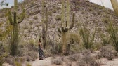 tucson : Slow motion young beautiful tourist woman looking back at camera among giant Saguaro cactus plants in Arizona desert.