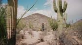 tucson : Slow motion camera moves towards young beautiful woman spinning happy among big Saguaro cactus national park desert. Stock Footage