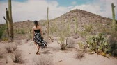 walk : Slow motion camera follows young beautiful tourist woman with wind blowing in dress exploring big Saguaro cactus desert.