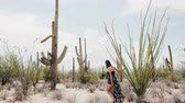 tucson : Epic slow motion wide shot, young happy tourist woman walks among big Saguaro cactus field in hot national park desert. Stock Footage