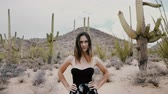 tucson : Slow motion camera zooms in on beautiful young woman posing with challenging look at amazing cactus national park USA. Stock Footage