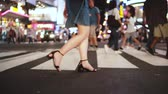 annunci : Slow motion lifestyle shot of beautiful young female legs walking across crowded street at night in Times Square, NY.