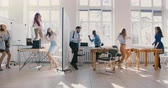 doorbraak : Slow motion dolly shot of business people dancing in light modern office party, multiethnic team celebrating success.