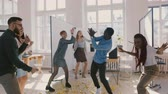doorbraak : Happy young multiethnic startup company colleagues celebrate achievements dancing at exciting office party slow motion. Stockvideo