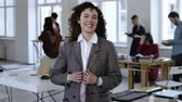 advogado : Medium portrait of young Caucasian business woman with curly hair, formal suit smiling happy at camera at modern office. Stock Footage