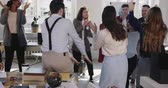 doorbraak : Fun young happy brunette female boss celebrating achievements dancing with multiethnic colleagues at modern office.