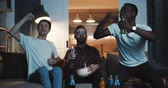 maço : Happy multiethnic male sport fans shout, celebrate win watching the game together at home with drinks slow motion.