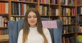 pohlednice : Brown-haired young women get valentines card, letter in white sweater on blue armchair, library background. Valentines Day. Dostupné videozáznamy