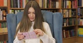canteiro de flores : Brown-haired young women get valentines card, letter in white sweater on blue armchair, library background. Valentines Day. Stock Footage