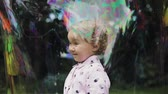 Little curly girl in huge bubble feeling happy. Slow motion. Bubble show.