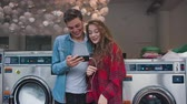 csillár : Beautiful couple in a laundry listen to the music on the phone, watching videos, stories. Handsome young man with stylish hairсut in jeans shirt. Woman with curly red hair in tartan shirt.