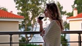 varanda : Woman stands on balcony and drinks wine Stock Footage