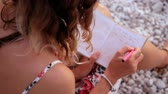 безмятежность : Close up view of a woman writing in her diary at sunset sitting on the beach Стоковые видеозаписи