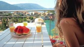 Young woman enjoying of scenic view during breakfast sitting on a balcony at beautiful island background