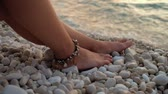 Close-up womans legs with a bracelet on pebble stones at the beach