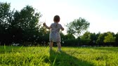 Little baby girl catching on green grass in summer. Slow Motion 120 fps, Happy childhood and Parenthood concept.
