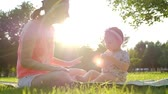 Little baby girl sitting on grass in summer Slow Motion 120 fps, Happy childhood and Parenthood concept.