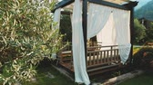 Outdoor wooden gazebo with white curtains. Garden pavilion on summer day.1920x1080 Full HD Slow motion video footage. Tracking shot. 影像素材