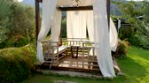 b roll : Outdoor wooden gazebo with white curtains. Garden pavilion on summer day.1920x1080 Full HD Slow motion video footage. Tracking shot. Stock Footage
