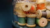 broderie : Closeup dolly shot of thread spools in a glass jar. Full hd 1080 footage