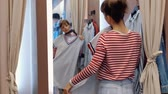 guarda roupa : Rear view of a pretty young woman in casual wear trying on things in a wardrobe room. Shopping mall concept on weekends and on sales days. Full hd 1080 footage Vídeos