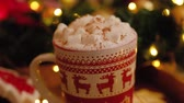 Close-up of a Christmas mug with cocoa with marshmallows and cinnamon standing near a Christmas tree and ginger cookies. Christmas and New Year atmosphere concept. 4k footage