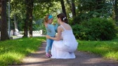 Young caring mother communicates with her charming little daughter in a blue suit while walking in the park on a sunny warm summer day. Child care concept. 4k footage Wideo