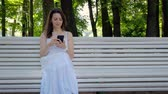 Beautiful young woman is typing a message in a smartphone surfing social networks sitting on a park bench on a warm sunny summer day. 4k footage