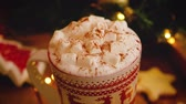 Close-up of a beautiful Christmas mug standing near a Christmas tree with cocoa marshmallows and cinnamon. Holiday and miracle atmosphere concept. 4k footage