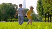 Little cute boy and girl play in the park on the green grass with toys on a sunny warm summer day. Concept of children walking outdoors. Full hd 1080 footage Wideo