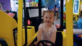 Portrait of a cheerful little girl joyfully playing with slot machine