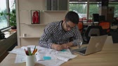 creative : Architect checking details and make notes on the paper plan. Documents and computer on the wooden table with equipment for drawing and draftsmanship. Male wearing in casual clothes work in modern creative office with big windows. Stock Footage
