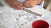 traçado : Woman architect correct design and draftsmanship on architectural sketch. On the wooden desk plan new building or house or flat. She using red pencil and line.Mixed race womens hands drawing on blueprint. Details of everyday designer work.