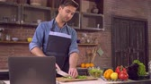 vegeterian : Man standing on the kitchen at home alone. Handsome husband cutting ingredients for salad. Happy smiling guy wearing an apron and blue shirt cooking dinner. On the cook table laptop with recipe dish with vegetables and glass with wine. Stock Footage