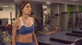 nutritious : Lady going fast and quenches thirst with special drink in gym. Beautiful member of the sports club walking on treadmill holding bottle with drink. Caucasian woman trains on cardio machines. Stock Footage
