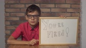 hirer : Portrait little boy showing whiteboard with handwriting word you are fired. Child with spectacles on strict face. Preadolescent wearing in casual red shirt. Schoolboy with happy friendly smile. Stock Footage