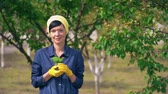 botany : Girl standing surrounded by trees. Smiling woman holding flowering flower. Grower wearing in uniform for gardening and yellow work safety gloves.