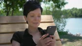 hipster : Portrait caucasian woman with short black hair using mobile outdoors. Smiling girl messaging sms on touch screen smart phone. Close up female outdoors near river and green trees.