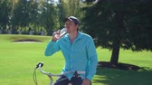 bike ride : Caucasian adult man sitting on bicycle drinking water outdoors in summertime. cheerful smiling men enjoy drink after cycling in park. Portrait male with nature landscape in sunny day. Stock Footage