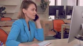 учреждение : cheerful manager has phone negotiation with client. adult businesswoman sitting at the working place using computer and giving consultation in modern office Стоковые видеозаписи